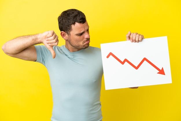 감소 통계 화살표 기호로 기호를 들고 나쁜 신호를하고 격리 된 보라색 배경 위에 브라질 남자