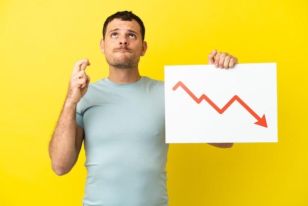교차하는 손가락으로 감소 통계 화살표 기호 기호를 들고 고립 된 보라색 배경 위에 브라질 남자