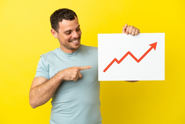 Бразильский мужчина на изолированном фиолетовом фоне держит табличку с растущим символом стрелки статистики и указывает на нее