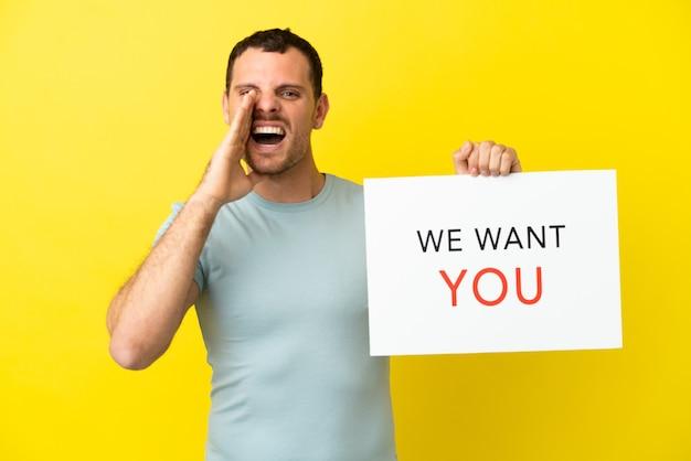 Бразильский мужчина на изолированном фиолетовом фоне держит доску we want you и кричит
