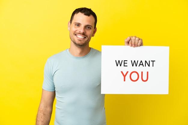 격리된 보라색 배경 위에 있는 브라질 남자가 행복한 표정으로 we want you 보드를 들고 있습니다.
