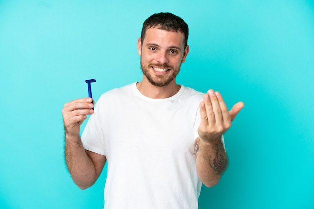 Brazilian man shaving his beard isolated on blue background inviting to come with hand. happy that you came