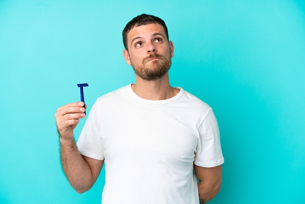 Бразильский мужчина бреет бороду на синем фоне и смотрит вверх