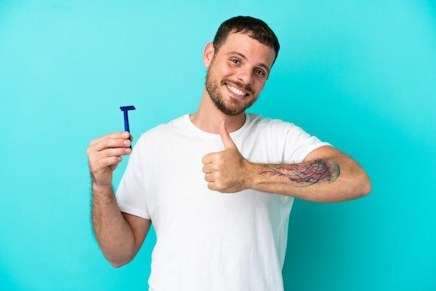 엄지손가락 제스처를 주는 파란색 배경에 고립 된 그의 수염을 면도 하는 브라질 남자