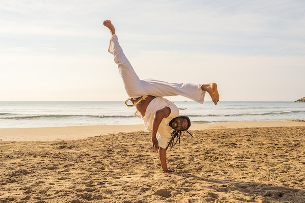 A brazilian man trains capoeira on the beach. - concept about people, lifestyle and sport. a boy performs martial the kick in the jump.
