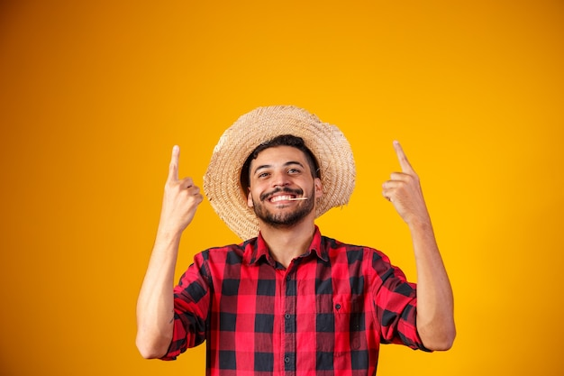 Brazilian man wearing typical clothes for the festa junina pointing to the side