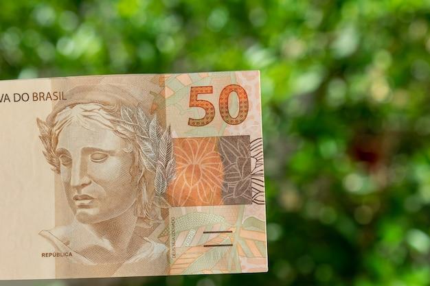 緑の焦点がぼけた背景を持つブラジルのお金の紙幣