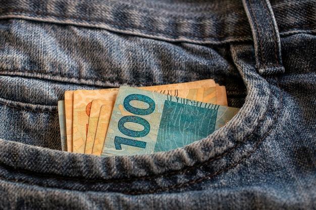 Brazilian money bills in jeans pocket