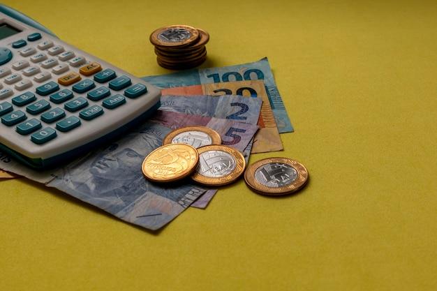 노란색 바탕에 브라질 돈 동전과 계산기 재정 제어 긴급 지원