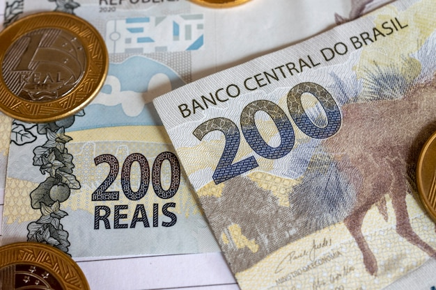 Brazilian money coins and calculator on yellow background financial control emergency assistance