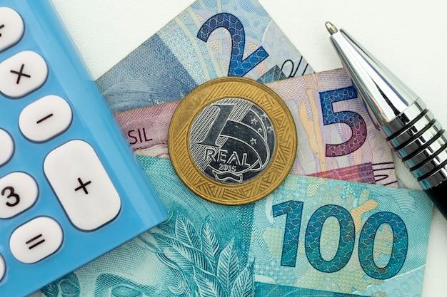 브라질 돈, 통화, 계산기 및 펜. 재정 관리 개념입니다.