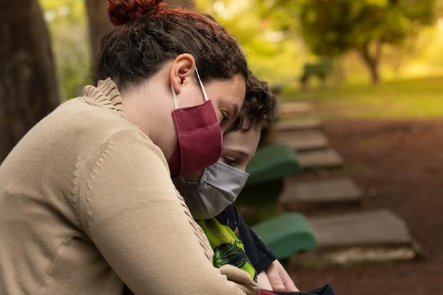Бразильские мать и сын обнимаются, разговаривают на скамейке в парке