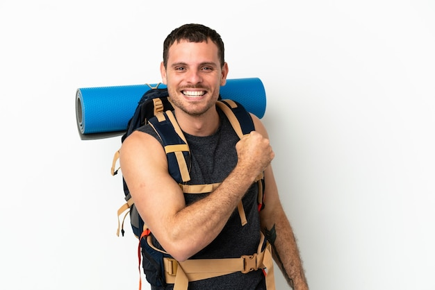 勝利を祝う孤立した白い背景の上に大きなバックパックを持つブラジルの登山家の男