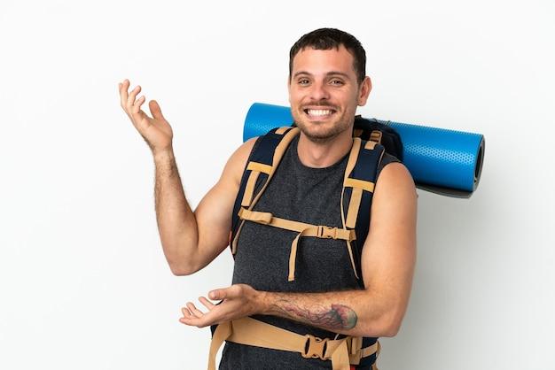 Бразильский альпинист с большим рюкзаком на изолированном белом фоне протягивает руки в сторону, приглашая приехать