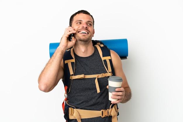 持ち帰り用のコーヒーと携帯電話を保持している孤立した白い背景の上に大きなバックパックを持つブラジルの登山家の男