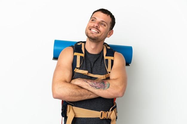 Бразильский альпинист с большим рюкзаком на изолированном белом фоне смотрит вверх, улыбаясь