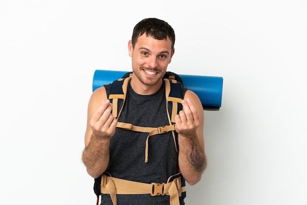 Бразильский альпинист с большим рюкзаком на изолированном белом фоне делает денежный жест