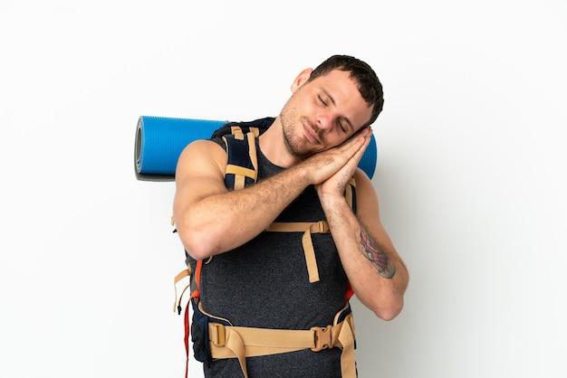 愛らしい表情で睡眠ジェスチャーを作る孤立した白い背景の上に大きなバックパックを持つブラジルの登山家の男