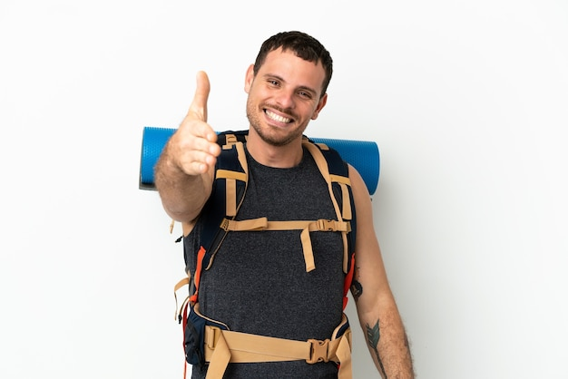 かなりの取引を閉じるために握手する孤立した白い背景の上に大きなバックパックを持つブラジルの登山家の男