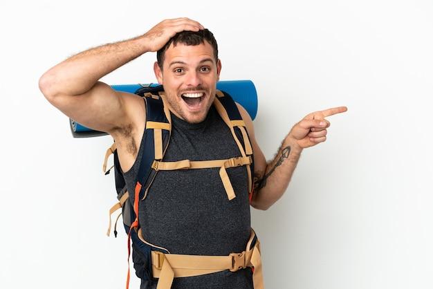 孤立した白い背景の上に大きなバックパックを持つブラジルの登山家の男は驚いて、人差し指を横に向けます