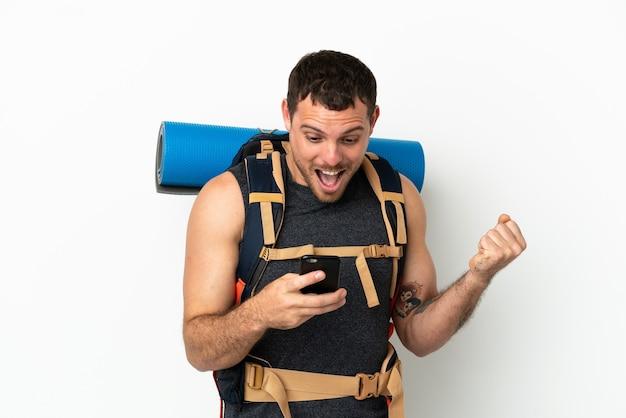 Бразильский альпинист с большим рюкзаком на изолированном белом фоне удивлен и отправляет сообщение