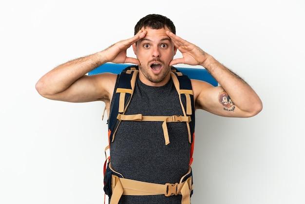 Бразильский альпинист с большим рюкзаком на изолированном белом фоне с удивленным выражением лица
