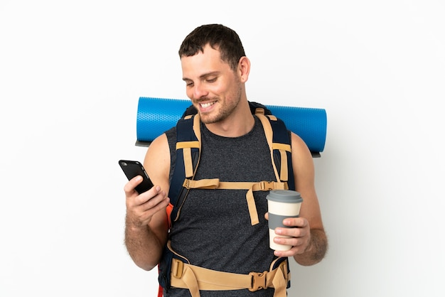 Brazilian mountaineer man with a big backpack over isolated white background holding coffee to take away and a mobile