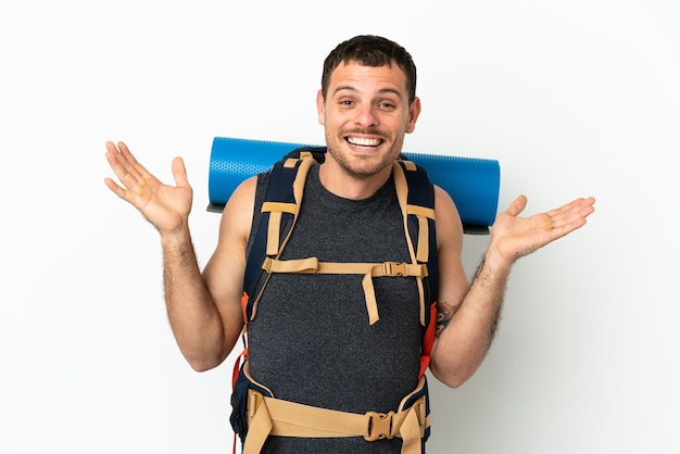 Brazilian mountaineer man with a big backpack over isolated white background with shocked facial expression