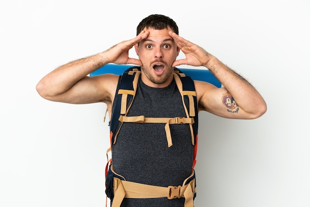 Brazilian mountaineer man with a big backpack over isolated white background with surprise expression