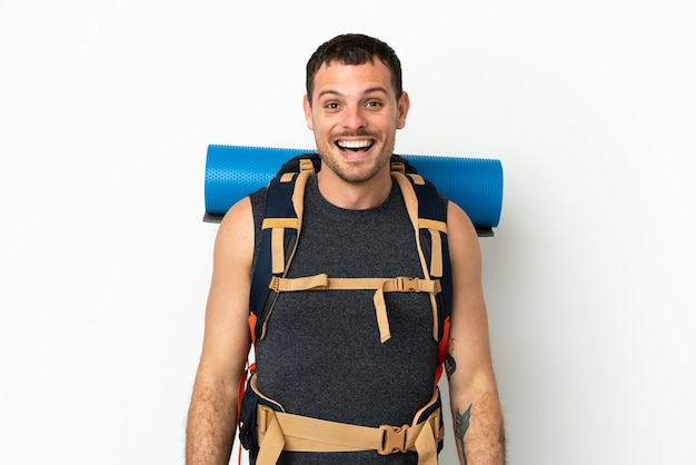 Brazilian mountaineer man with a big backpack over isolated white background with surprise facial expression
