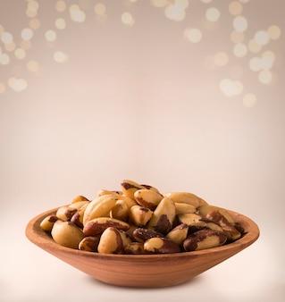 Brazilian nuts: castanha do para into a bowl on beige background.