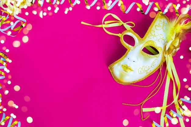 ブラジルまたはベネチアのカーニバルピンクの背景に金色の曲がりくねった明るいマスク