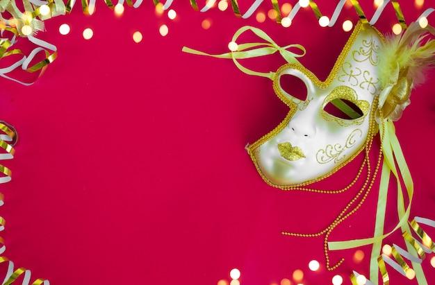 ブラジルまたはベネチアのカーニバル黄金の曲がりくねった赤い背景の明るいマスク