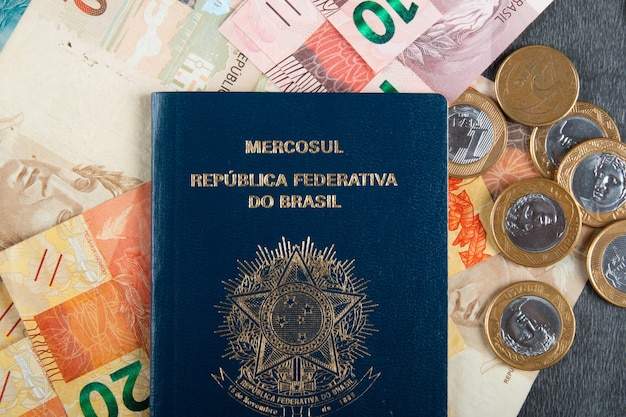 Brazilian passport with real bills and coins.