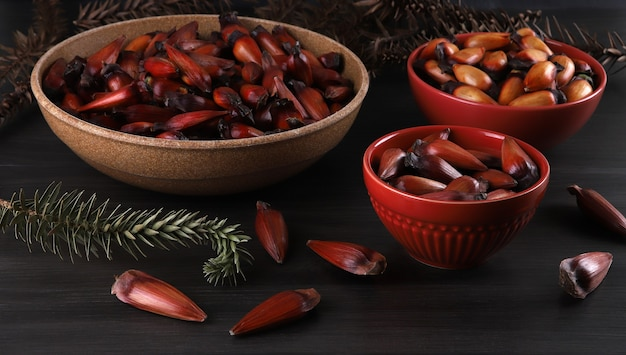 회색 나무 바탕에 갈색과 빨간색 나무 그릇에 브라질 피니언 너트.