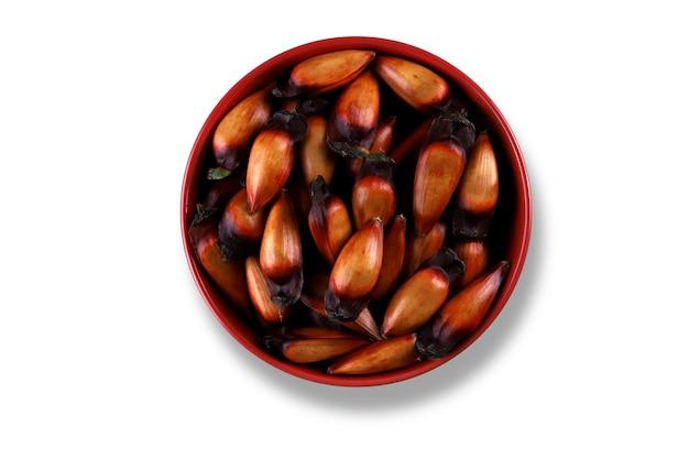 흰색 바탕에 갈색과 빨간색 나무 그릇에 브라질 피니언 너트.