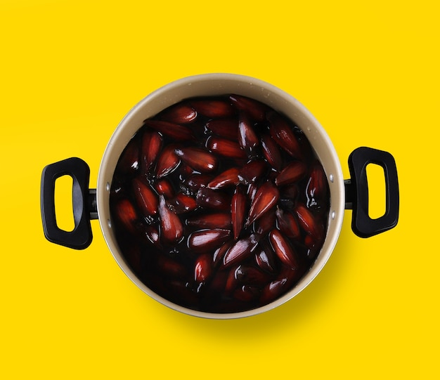 노란색 바탕에 갈색과 빨간색 나무 그릇에 브라질 피니언 너트.