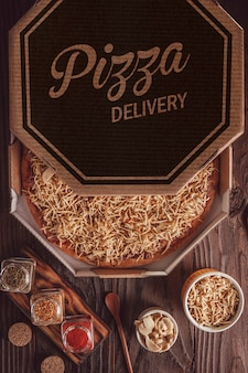 Brazilian pizza with mozzarella, beef stroganoff and potato sticks in a delivery box (pizza de strogonoff de carne) - top view.
