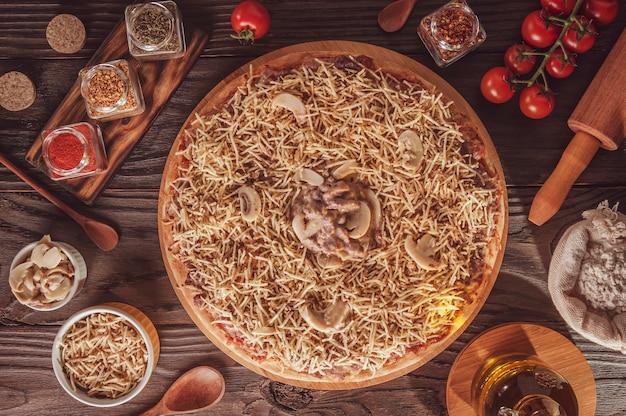 Brazilian pizza with mozzarella, beef stroganoff and potato sticks (pizza de strogonoff de carne) - top view.