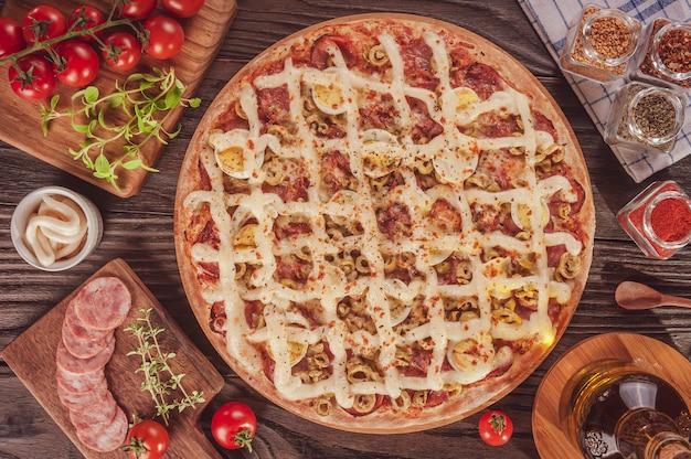 モッツァレラチーズ、カラブレーゼソーセージ、卵、カトゥピリ、オリーブ、オレガノを使ったブラジルのピザ(pizza especial de calabresa)-上面図。