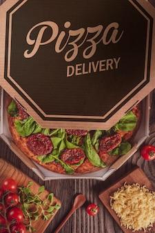 トマトソース、モッツァレラチーズ、ルッコラ、ドライトマト、オレガノを配達ボックスに入れたブラジルのピザ(pizza de rucula com tomate seco)-上面図。