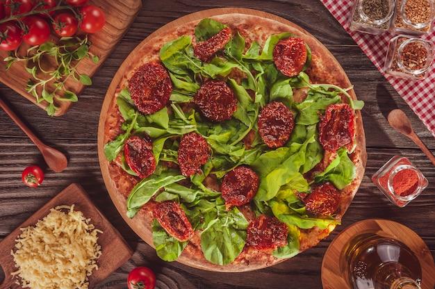 トマトソース、モッツァレラチーズ、ルッコラ、ドライトマト、オレガノを添えたブラジルのピザ(pizza de rucula com tomate seco)-上面図。