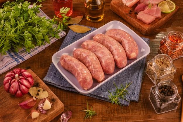 향신료와 재료와 흰 접시에 브라질 돼지 다리 소시지