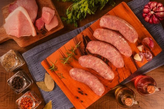 향신료와 재료와 나무 커팅 보드에 브라질 돼지 다리 소시지