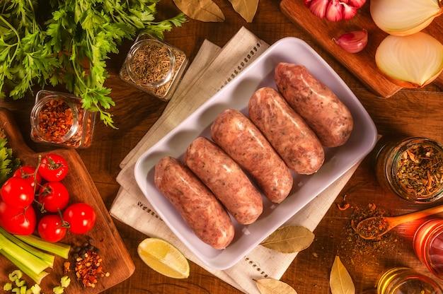 Бразильская свиная колбаса с чимичурри на белой тарелке со специями и ингредиентами