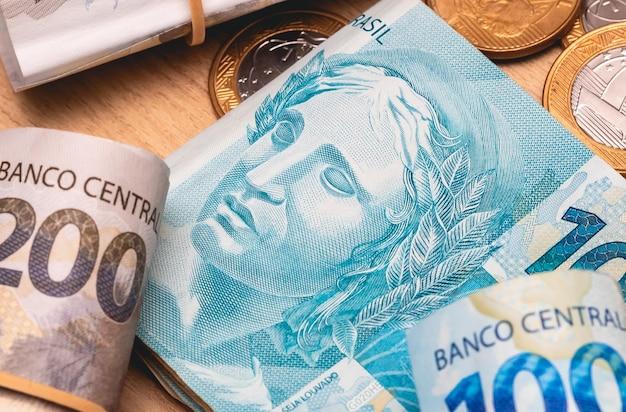 매크로 사진의 나무 테이블에 있는 브라질 실제 지폐와 동전