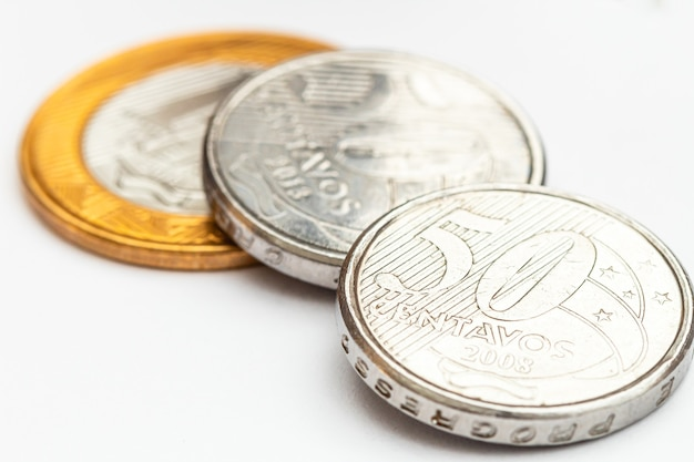 Brazilian real coins on white paper in macro photography for finance and savings concept