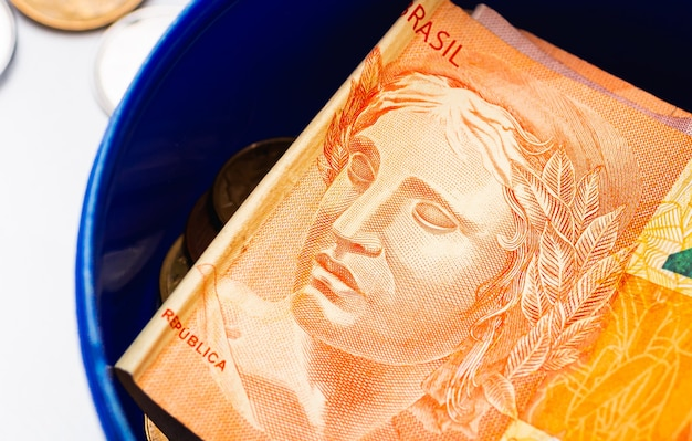 A brazilian real note inside a money bank in a close up photo