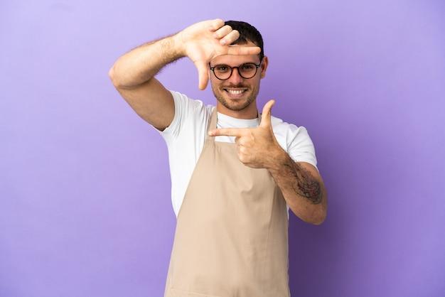 Официант бразильского ресторана на изолированном фиолетовом фоне, фокусируя лицо. обрамление символа