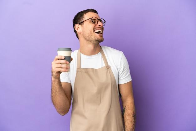 Официант бразильского ресторана на изолированном фиолетовом фоне счастливы и улыбаются